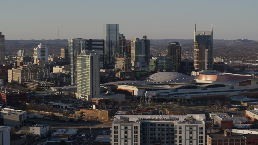 5.7K stock footage aerial video reverse view of city's tall skyline beside Nashville Music City Center in Downtown Nashville, Tennessee Aerial Stock Footage | DX0002_114_040