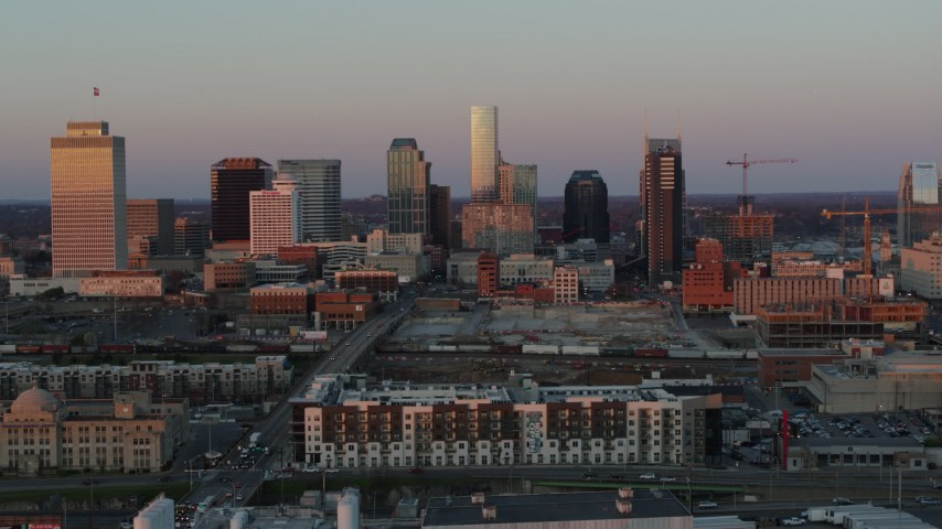 5.7K stock footage aerial video descend near apartments, focus on city's skyline at sunset in Downtown Nashville, Tennessee Aerial Stock Footage | DX0002_115_009