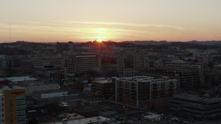 5.7K stock footage aerial video slowly descend and orbit hospital with view of setting sun, Nashville, Tennessee Aerial Stock Footage | DX0002_115_014
