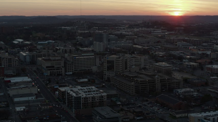 5.7K stock footage aerial video ascend and fly away from hospital with view of setting sun, Nashville, Tennessee Aerial Stock Footage | DX0002_115_015