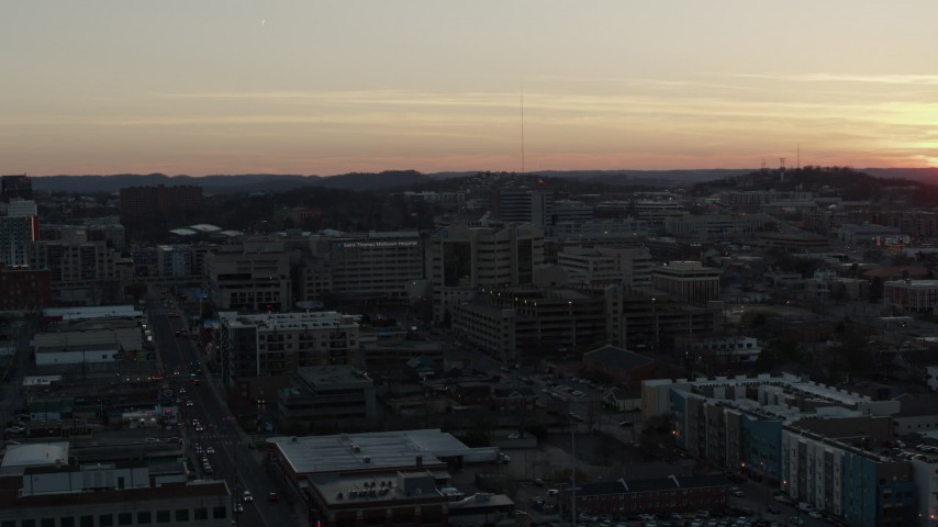 5.7K stock footage aerial video descend near a hospital complex with view of setting sun, Nashville, Tennessee Aerial Stock Footage | DX0002_115_016