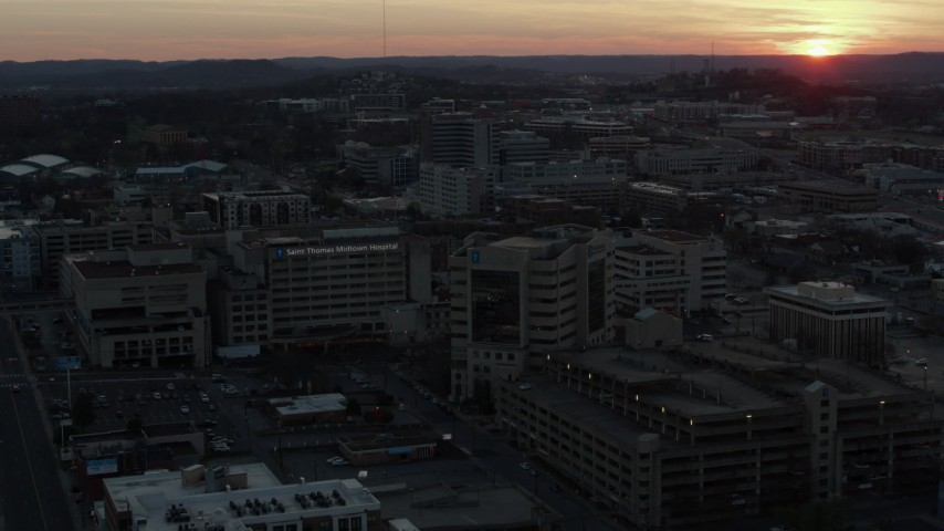 5.7K stock footage aerial video approach hospital complex and ascend with view of setting sun, Nashville, Tennessee Aerial Stock Footage | DX0002_115_017