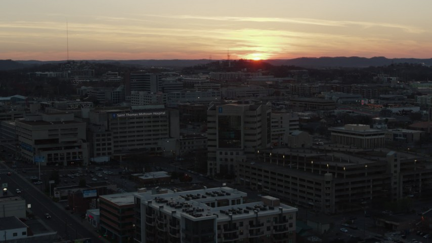 5.7K stock footage aerial video a hospital complex with view of setting sun, seen during descent and orbit, Nashville, Tennessee Aerial Stock Footage | DX0002_115_018