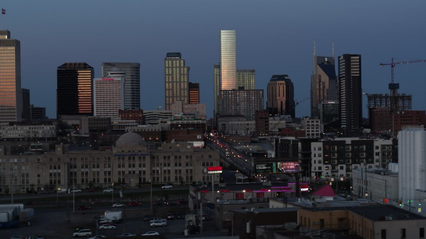 5.7K stock footage aerial video descend and flyby Church Street with view of city's skyline at twilight in Downtown Nashville, Tennessee Aerial Stock Footage | DX0002_115_022