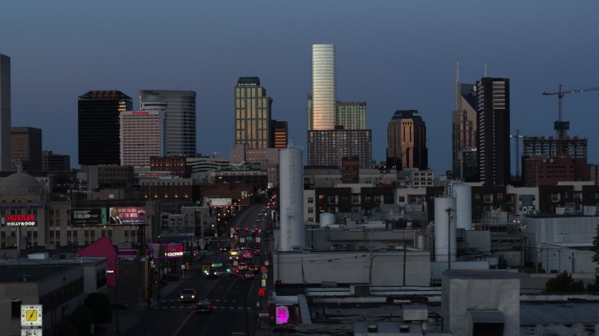 5.7K stock footage aerial video flashing lights on Church Street and view of city's skyline at twilight in Downtown Nashville, Tennessee Aerial Stock Footage | DX0002_115_023