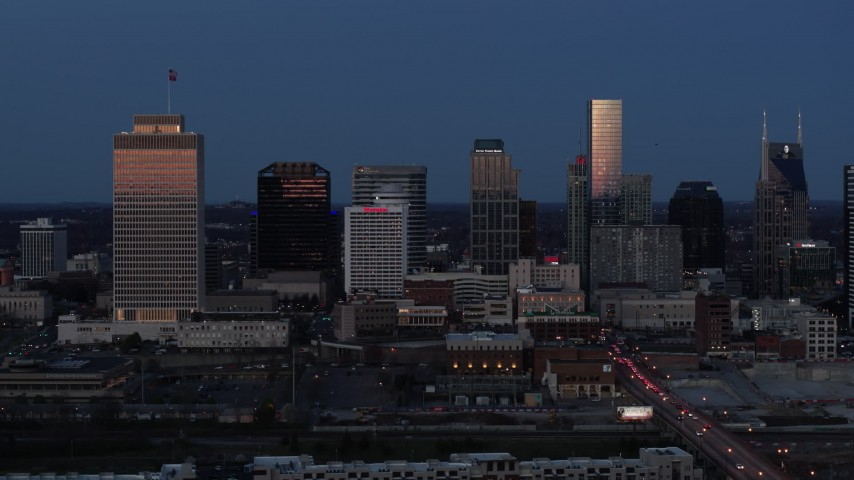 5.7K stock footage aerial video flying by skyscrapers reflecting light in the city skyline at twilight in Downtown Nashville, Tennessee Aerial Stock Footage | DX0002_115_026