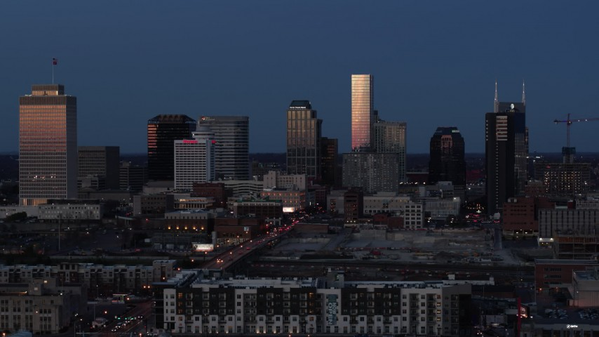 5.7K stock footage aerial video passing by skyscrapers reflecting light in the city skyline at twilight in Downtown Nashville, Tennessee Aerial Stock Footage | DX0002_115_028
