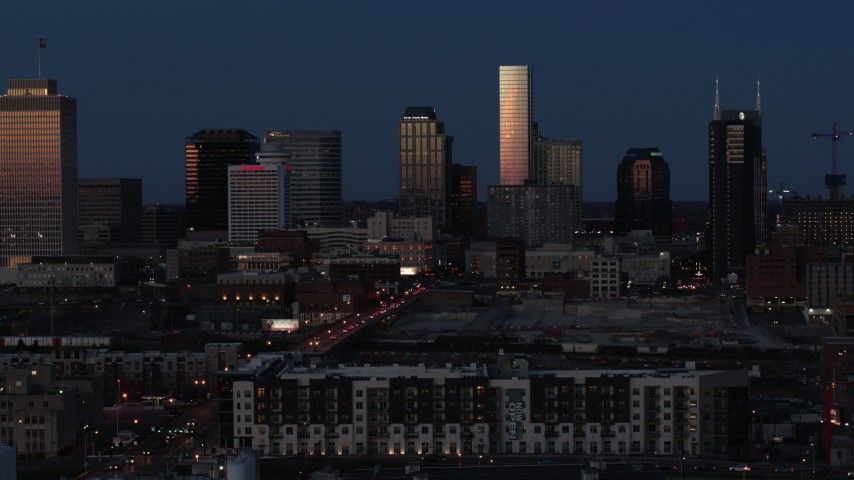 5.7K stock footage aerial video passing skyscrapers reflecting light in the city skyline at twilight before descent, Downtown Nashville, Tennessee Aerial Stock Footage | DX0002_115_031