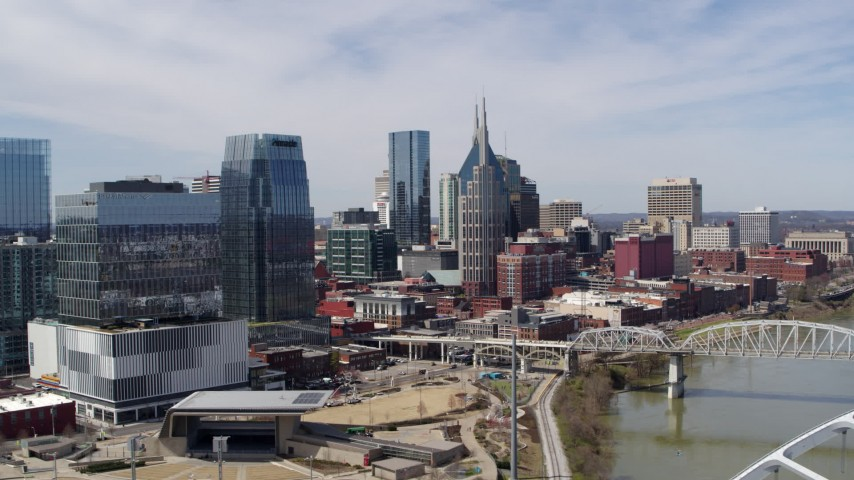 5.7K stock footage aerial video flying past skyscrapers near a bridge spanning the river in Downtown Nashville, Tennessee Aerial Stock Footage | DX0002_116_003