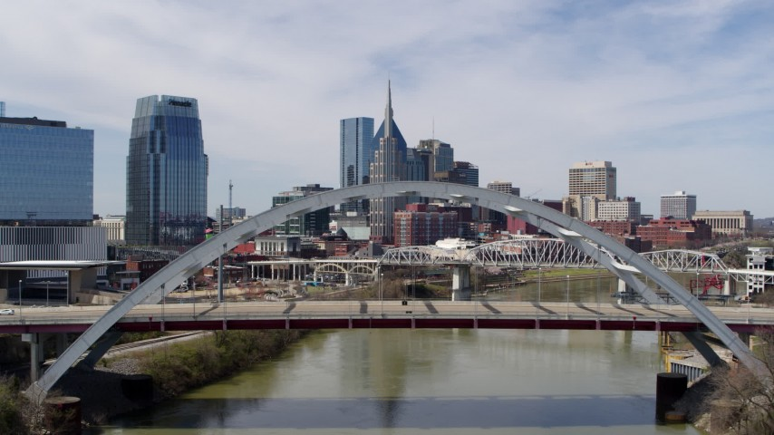 5.7K stock footage aerial video of tall skyscrapers seen from a bridge spanning the river in Downtown Nashville, Tennessee Aerial Stock Footage DX0002_116_004 | Axiom Images