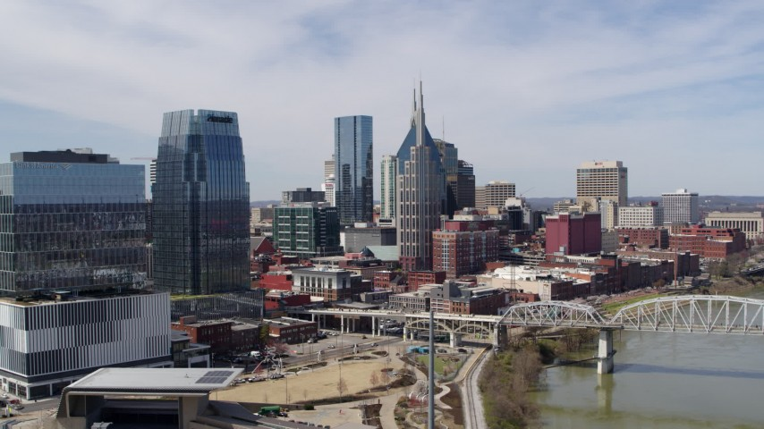 5.7K stock footage aerial video of flying by skyscrapers and reveal a bridge over the river in Downtown Nashville, Tennessee Aerial Stock Footage | DX0002_116_012