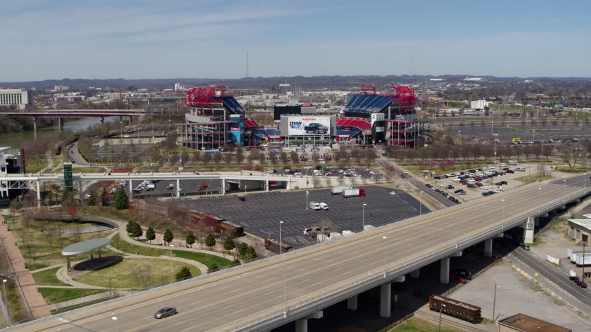 5.7K stock footage aerial video of Nissan Stadium while ascending near a bridge in Nashville, Tennessee Aerial Stock Footage | DX0002_116_020