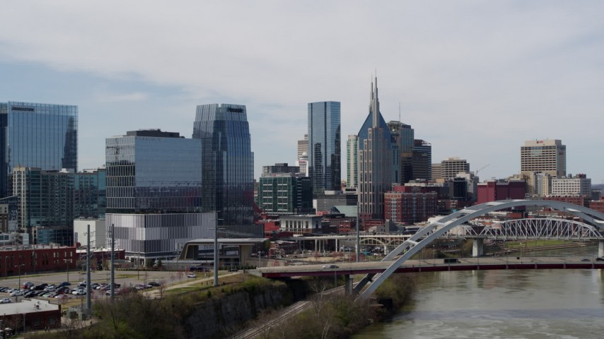 5.7K stock footage aerial video of office high-rise and skyscrapers seen from river and bridge in Downtown Nashville, Tennessee Aerial Stock Footage | DX0002_116_022