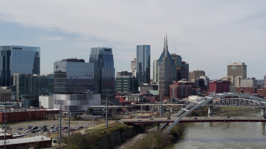 5.7K stock footage aerial video of office high-rise and tall skyscrapers seen from near river and bridge in Downtown Nashville, Tennessee Aerial Stock Footage | DX0002_116_023