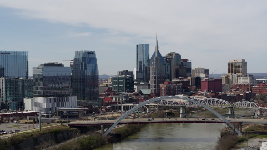 5.7K stock footage aerial video of slowly passing a river and bridge, focus on skyscrapers in Downtown Nashville, Tennessee Aerial Stock Footage | DX0002_116_024