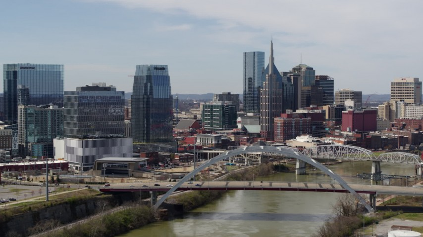 5.7K stock footage aerial video of slowly flying by the river and bridge, focus on skyscrapers in Downtown Nashville, Tennessee Aerial Stock Footage | DX0002_116_025