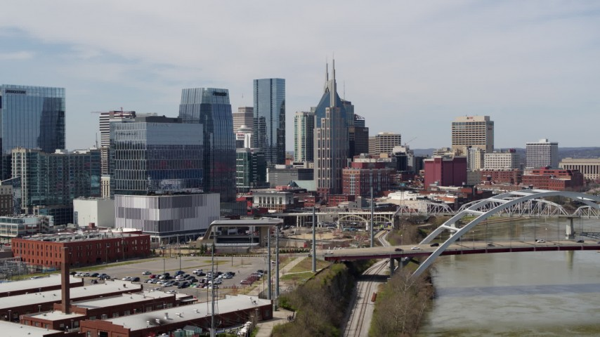 5.7K stock footage aerial video of descending by the river and bridge, focus on skyscrapers in Downtown Nashville, Tennessee Aerial Stock Footage | DX0002_116_026