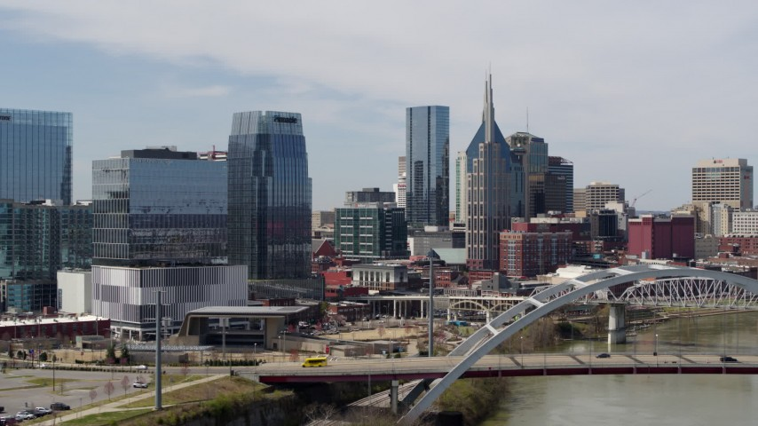 5.7K stock footage aerial video flyby the river and bridge, approach office building and skyscrapers in Downtown Nashville, Tennessee Aerial Stock Footage | DX0002_116_027