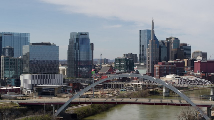 5.7K stock footage aerial video fly away from river and bridge, office high-rise and skyscrapers in Downtown Nashville, Tennessee Aerial Stock Footage | DX0002_116_028