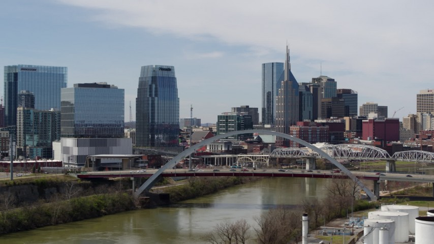 5.7K stock footage aerial video approach river and bridge, and skyscrapers near the Cumberland River in Downtown Nashville, Tennessee Aerial Stock Footage DX0002_116_029