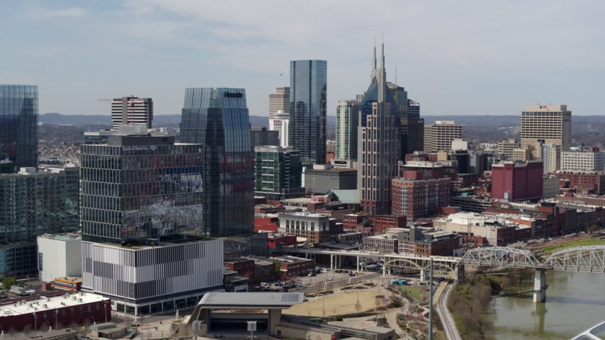 5.7K stock footage aerial video flyby Cumberland River and bridge, closer view of office high-rise and skyscrapers in Downtown Nashville, Tennessee Aerial Stock Footage | DX0002_116_030