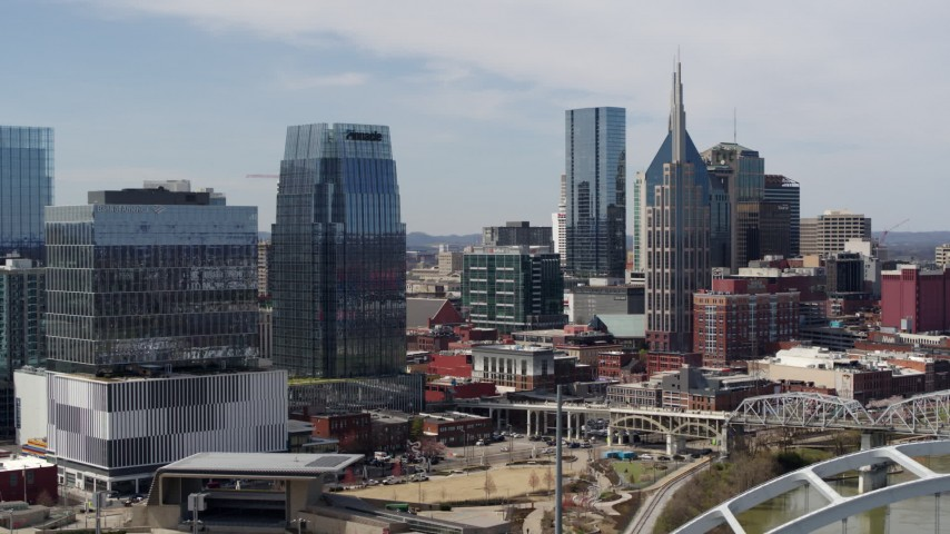 5.7K stock footage aerial video descend and orbit office high-rise and skyscrapers, seen from the river in Downtown Nashville, Tennessee Aerial Stock Footage | DX0002_116_031
