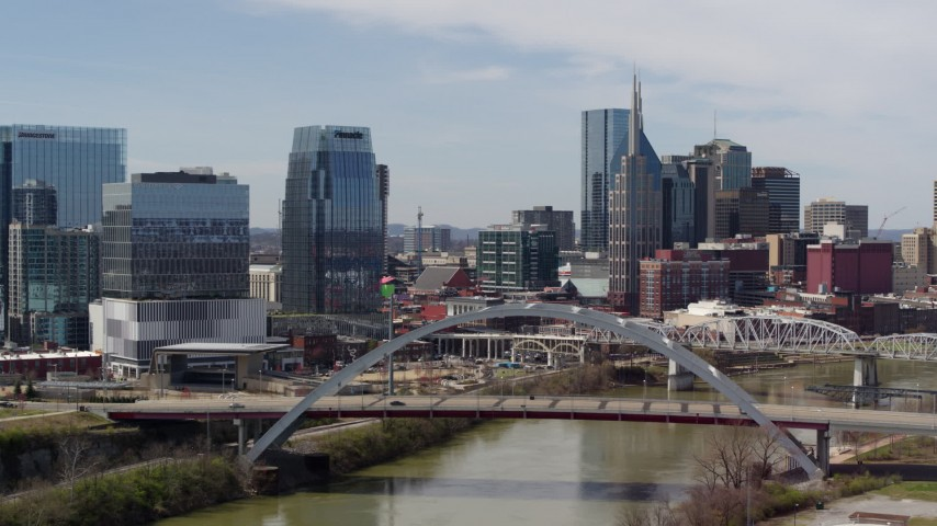 5.7K stock footage aerial video reverse view of office high-rise and skyscrapers, reverse bridge on the river in Downtown Nashville, Tennessee Aerial Stock Footage | DX0002_116_032