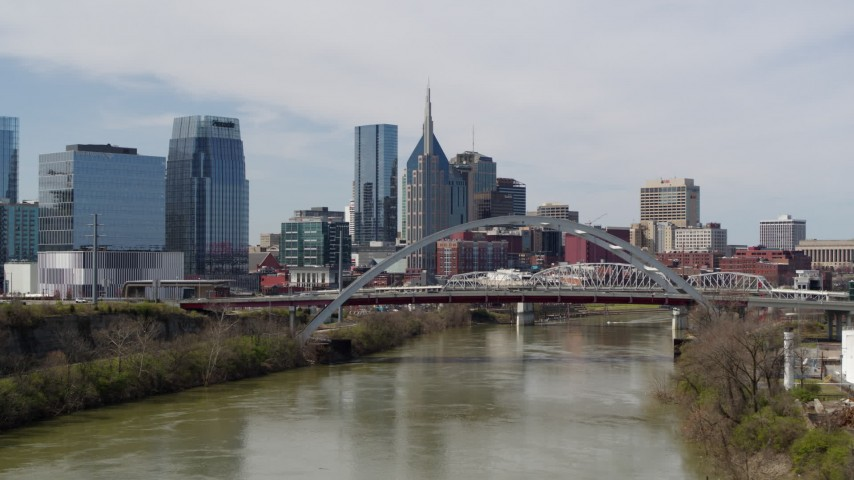 5.7K stock footage aerial video flyby and approach bridge on Cumberland River near skyscrapers in Downtown Nashville, Tennessee Aerial Stock Footage DX0002_116_033