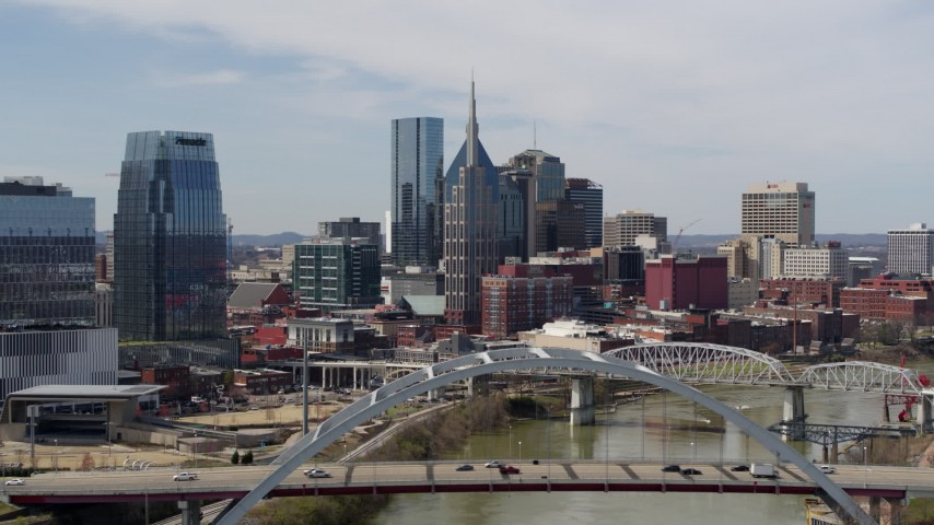 5.7K stock footage aerial video of a reverse view the AT&T Building seen from a bridge and the river in Downtown Nashville, Tennessee Aerial Stock Footage | DX0002_116_036