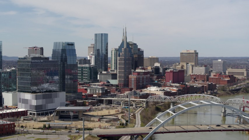 5.7K stock footage aerial video of the AT&T Building seen while flying by a bridge and the river in Downtown Nashville, Tennessee Aerial Stock Footage | DX0002_116_037
