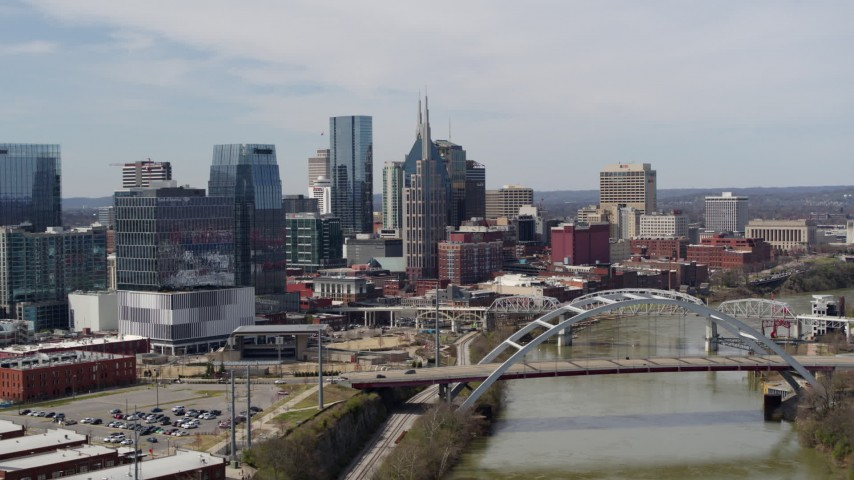 5.7K stock footage aerial video of the city's tall skyscrapers and a bridge on the Cumberland River in Downtown Nashville, Tennessee Aerial Stock Footage DX0002_116_038