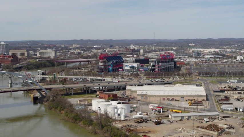 5.7K stock footage aerial video of Nissan Stadium near bridge, seen from Cumberland River in Nashville, Tennessee Aerial Stock Footage | DX0002_116_042