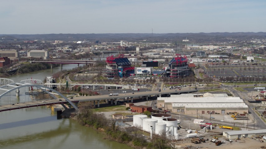 5.7K stock footage aerial video wide orbit of Nissan Stadium near bridge, seen from Cumberland River in Nashville, Tennessee Aerial Stock Footage | DX0002_116_043