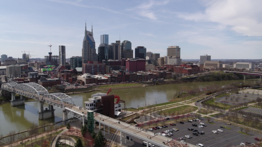 5.7K stock footage aerial video of the city's riverfront skyscrapers seen from the pedestrian bridge, Downtown Nashville, Tennessee Aerial Stock Footage | DX0002_117_002
