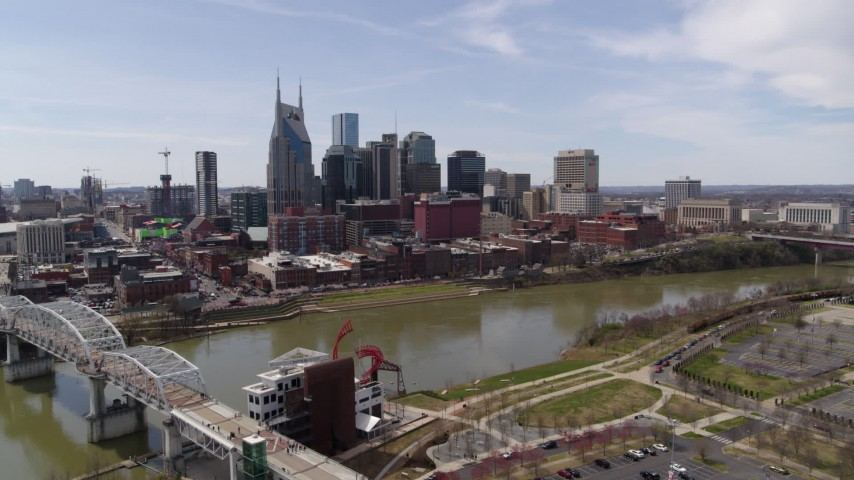 5.7K stock footage aerial video reverse view of the city's riverfront skyscrapers, descend near pedestrian bridge, Downtown Nashville, Tennessee Aerial Stock Footage | DX0002_117_004