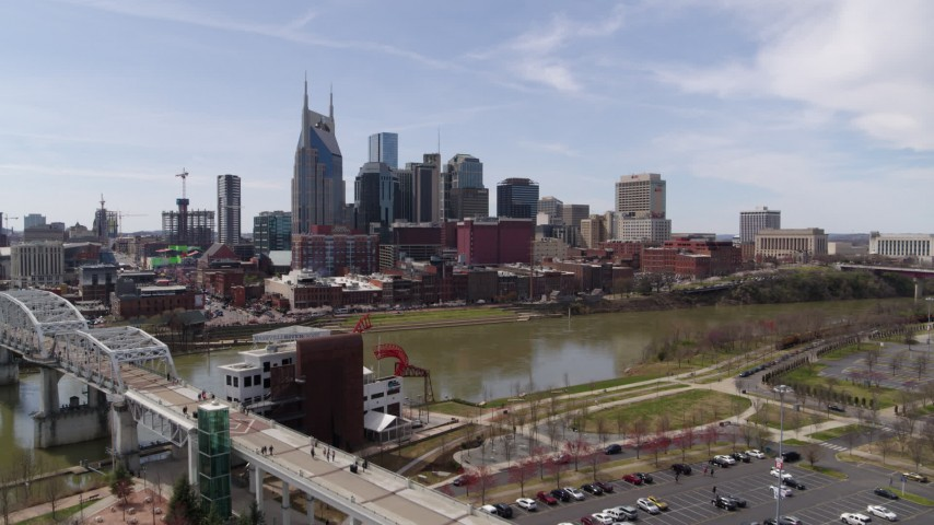 5.7K stock footage aerial video fly toward the city's riverfront skyscrapers from the pedestrian bridge, Downtown Nashville, Tennessee Aerial Stock Footage | DX0002_117_005