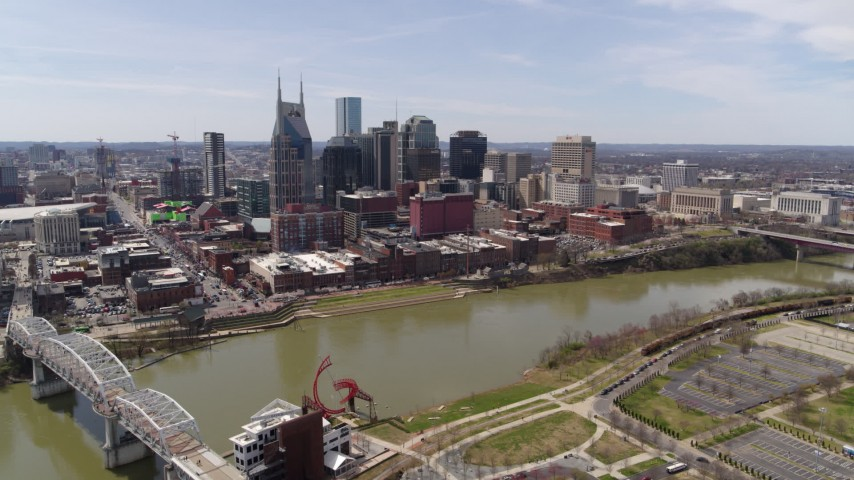 5.7K stock footage aerial video approach the city's riverfront skyscrapers across the Cumberland River, Downtown Nashville, Tennessee Aerial Stock Footage | DX0002_117_007