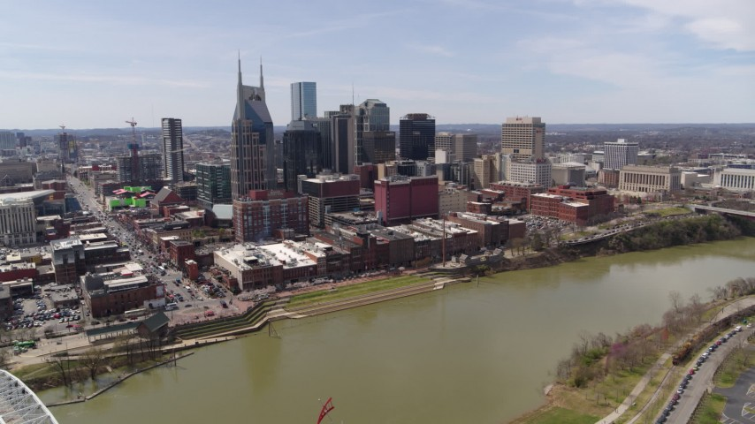 5.7K stock footage aerial video wide orbit of the city's riverfront skyscrapers across the Cumberland River, Downtown Nashville, Tennessee Aerial Stock Footage | DX0002_117_008