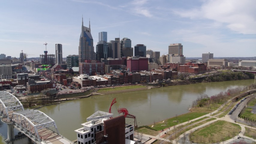 5.7K stock footage aerial video orbiting city's riverfront skyscrapers across the Cumberland River, seen from pedestrian bridge, Downtown Nashville, Tennessee Aerial Stock Footage | DX0002_117_009