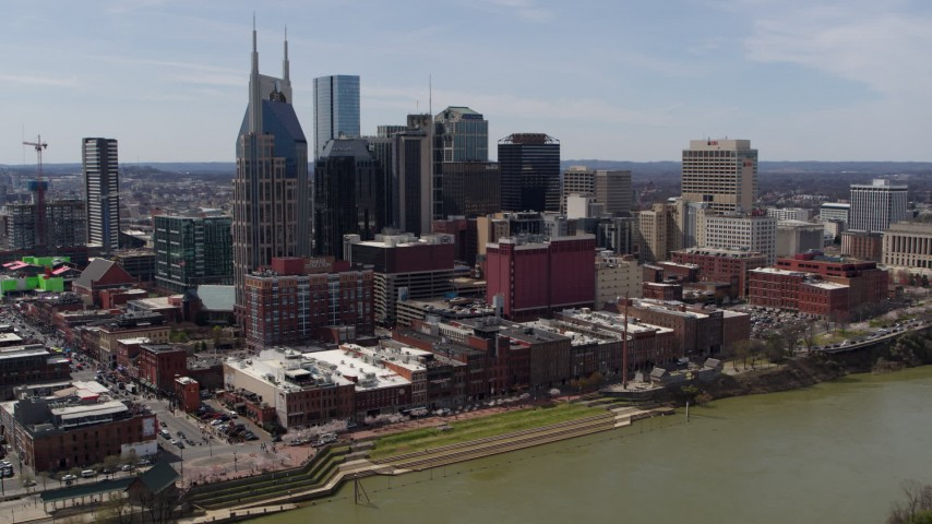 5.7K stock footage aerial video the city's skyline overlooking the Cumberland River, descend near pedestrian bridge, Downtown Nashville, Tennessee Aerial Stock Footage | DX0002_117_021