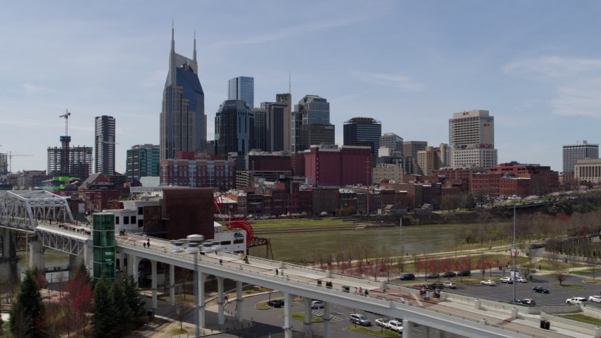 5.7K stock footage aerial video city's skyline overlooking the Cumberland River, descend and flyby pedestrian bridge, Downtown Nashville, Tennessee Aerial Stock Footage | DX0002_117_023