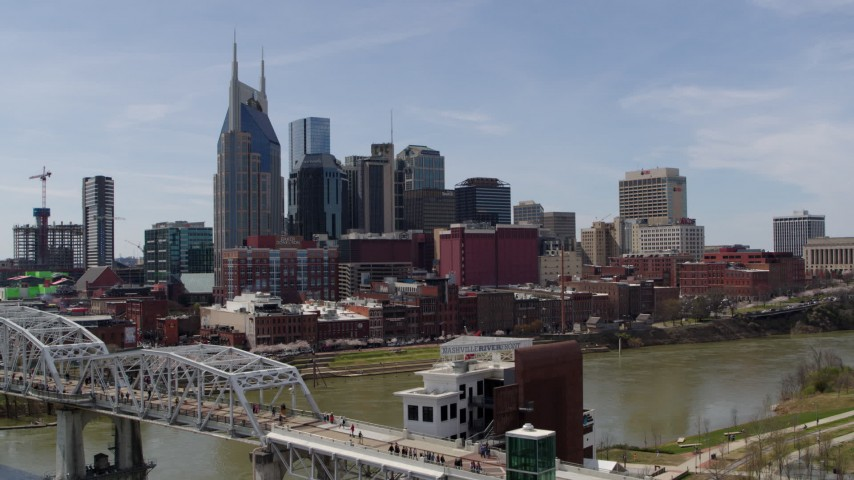 5.7K stock footage aerial video ascend by pedestrian bridge, focus on city's skyline, Downtown Nashville, Tennessee Aerial Stock Footage | DX0002_117_024