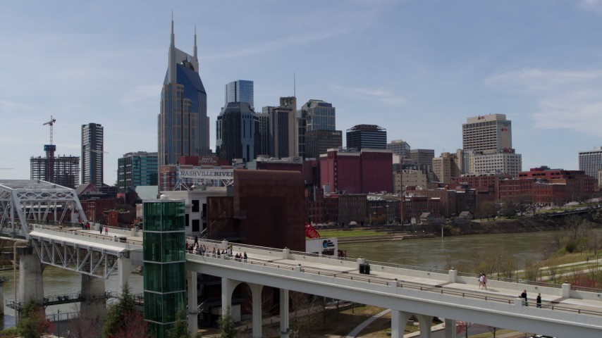 5.7K stock footage aerial video descend by pedestrian bridge with view of city's skyline, Downtown Nashville, Tennessee Aerial Stock Footage | DX0002_117_025