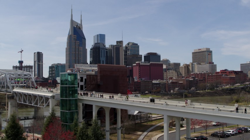 5.7K stock footage aerial video ascend by pedestrian bridge with view of city's skyline, Downtown Nashville, Tennessee Aerial Stock Footage | DX0002_117_026