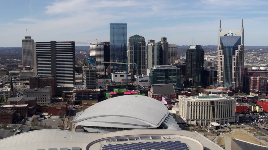 5.7K stock footage aerial video of flying by the city's skyline behind the arena, Downtown Nashville, Tennessee Aerial Stock Footage | DX0002_117_034