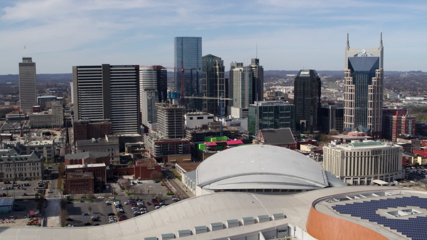 5.7K stock footage aerial video of a stationary view of the city's skyline behind the arena, Downtown Nashville, Tennessee Aerial Stock Footage | DX0002_117_035