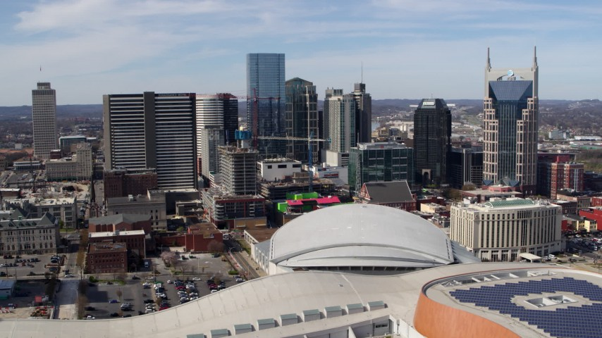 5.7K stock footage aerial video of flying by the city's skyline behind the arena and hotel, Downtown Nashville, Tennessee Aerial Stock Footage | DX0002_117_036
