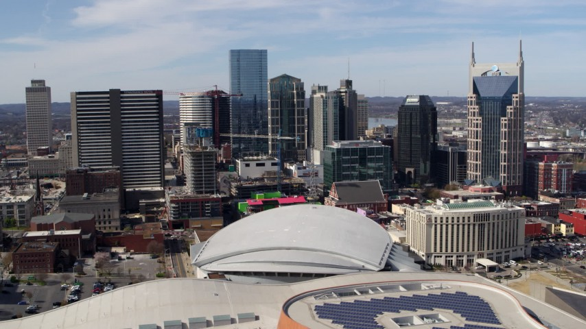 5.7K stock footage aerial video passing the city's skyline behind the arena and hotel, Downtown Nashville, Tennessee Aerial Stock Footage | DX0002_117_040