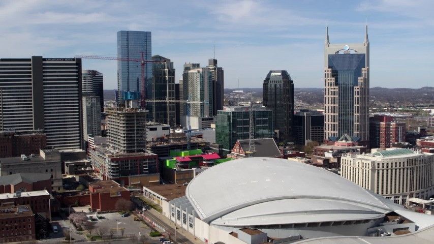 5.7K stock footage aerial video of flying by Bridgestone Arena with a view of the skyline, Downtown Nashville, Tennessee Aerial Stock Footage DX0002_117_043