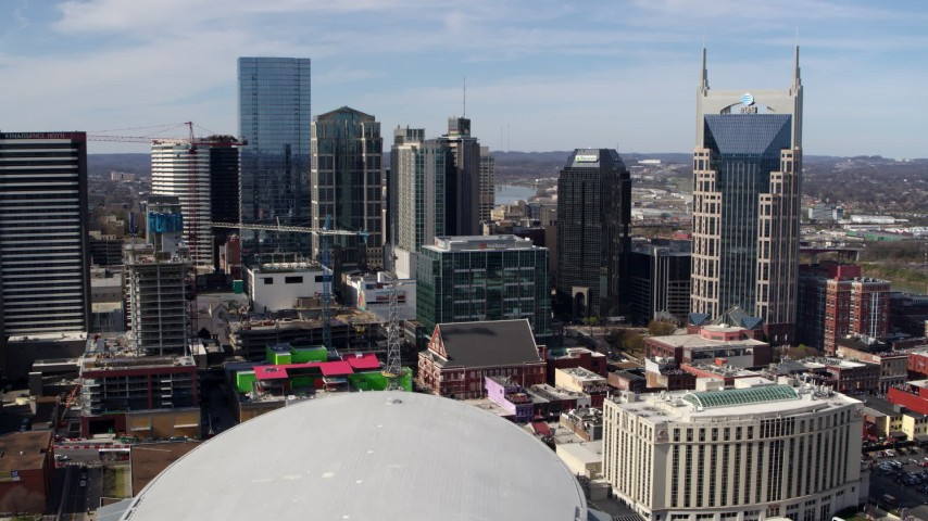 5.7K stock footage aerial video of passing by city's skyline, seen from Bridgestone Arena, Downtown Nashville, Tennessee Aerial Stock Footage | DX0002_117_044